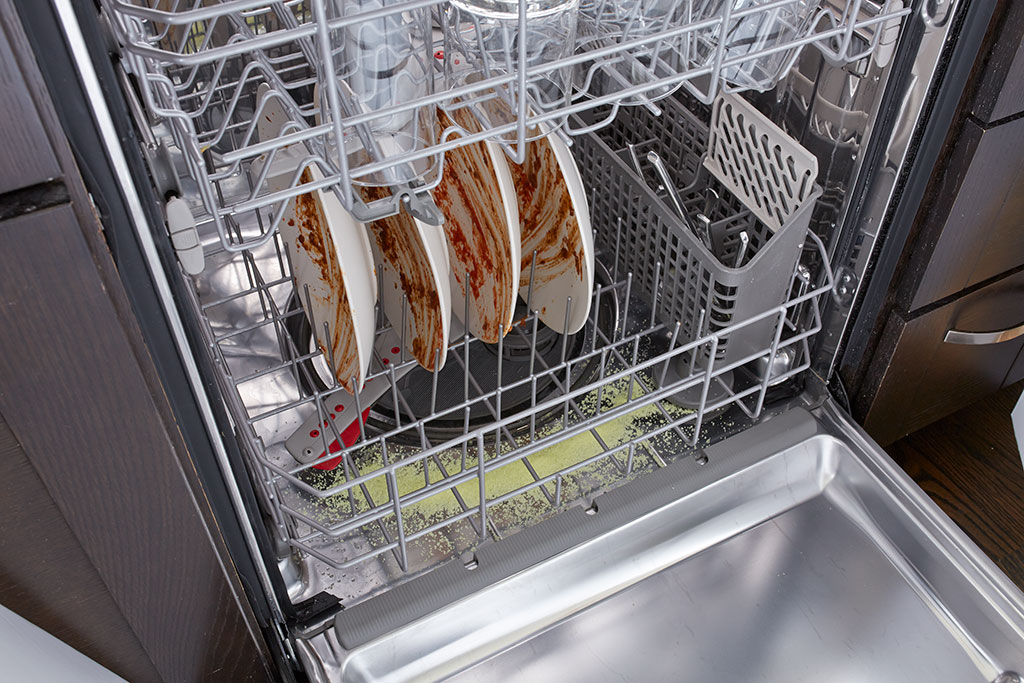Dishwasher with Dirty Dishes and Glisten detergent booster in bottom