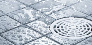 White plastic floor drain with water flowing toward it over gray tiles