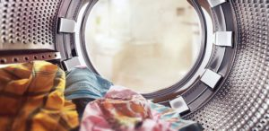 Stainless steel washing machine interior with clean laundry inside
