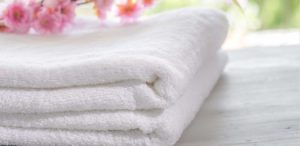Stack of white towels with pink flowers on top