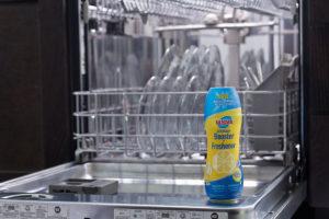 Glisten dishwasher detergent booster bottle in open dishwasher with dishes