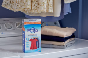 Woolite home dry cleaning kit on washer with clean laundry
